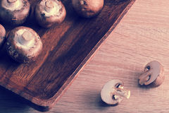 Fresh raw brown chestnut mushrooms whole in square wooden plate Stock Photography