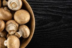 Fresh raw brown meadow on black wood. Fresh brown champignons in a wooden bowl top view on black wood background raw mushrooms Royalty Free Stock Image