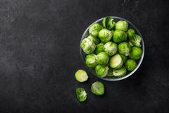 Fresh raw brussel sprouts in glass bowl. Dark background. Top view Royalty Free Stock Photo