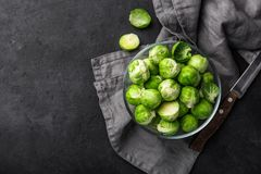 Fresh raw brussel sprouts in glass bowl. Dark background. Top view Royalty Free Stock Photos