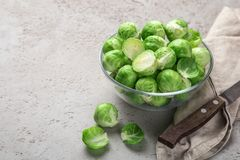 Fresh raw brussel sprouts in glass bowl. Grey background. selective focus Stock Photo