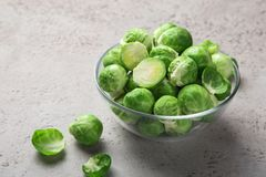 Fresh raw brussel sprouts in glass bowl. Grey background. selective focus Royalty Free Stock Photo