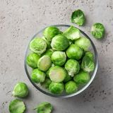 Fresh raw brussel sprouts in glass bowl. Grey background. Top view Stock Images