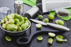 Fresh raw brussels sprouts on a black wooden table. Ingredients of a vegetarian dish Royalty Free Stock Photography