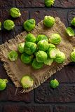 Fresh raw brussels sprouts on a old stone rustic table.  Stock Photo