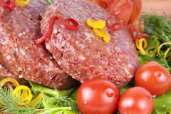 Fresh raw burger cutlet with herbs and tomatoes. Fresh raw burger cutlet with herbs pepper and tomatoes Stock Photography