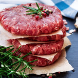 Fresh raw burger cutlets. From the farmers market on a black grunge table. Selective focus Royalty Free Stock Image
