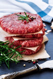 Fresh raw burger cutlets. From the farmers market on a black grunge table. Selective focus Stock Images