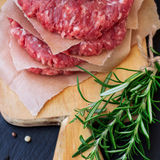 Fresh raw burger cutlets. From the farmers market on a black grunge table. Selective focus Stock Photography