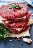 Fresh raw burger cutlets. From the farmers market on a black grunge table. Selective focus Royalty Free Stock Photos