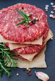 Fresh raw burger cutlets. From the farmers market on a black grunge table. Selective focus Royalty Free Stock Photography