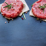 Fresh raw burger cutlets. From the farmers market on a black grunge table. Selective focus, copy space Royalty Free Stock Images