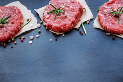 Fresh raw burger cutlets. From the farmers market on a black grunge table. Selective focus, copy space Stock Images