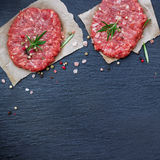 Fresh raw burger cutlets. From the farmers market on a black grunge table. Selective focus, copy space, top view Stock Photo
