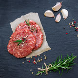 Fresh raw burger cutlets. From the farmers market on a black grunge table. Selective focus, flat lay Royalty Free Stock Photo