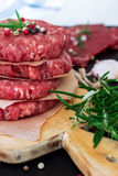 Fresh raw burger cutlets. From the farmers market on a rustic cutting board. Selective focus Royalty Free Stock Images