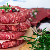 Fresh raw burger cutlets. From the farmers market on a rustic cutting board. Selective focus Royalty Free Stock Photo