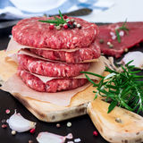Fresh raw burger cutlets. From the farmers market on a rustic cutting board. Selective focus Stock Images