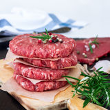 Fresh raw burger cutlets. From the farmers market on a rustic cutting board. Selective focus Royalty Free Stock Photos