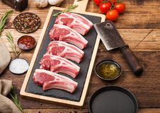 Fresh raw butchers lamb beef cutlets on chopping board with vintage meat hatchet and hammer on wooden background.Salt, pepper and. Oil with tomatoes and garlic stock photos