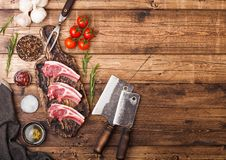 Fresh raw butchers lamb beef cutlets on chopping board with vintage meat hatchets on wooden background.Salt, pepper and oil with. Tomatoes and garlic and royalty free stock photo