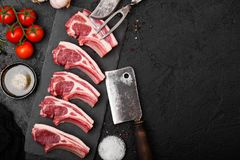 Fresh raw butchers lamb beef cutlets on stone board with vintage meat fork and knife and hatchet on black background.Salt, pepper. And oil with tomatoes and stock photography