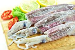Fresh raw calamari. And salad on chopping board Stock Photo