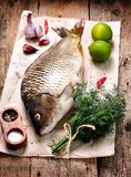 Fresh raw carp fish with lime, dill and garlic on old wooden background. Food Stock Photography