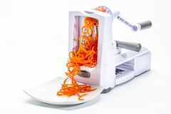 Fresh raw carrot spiralized spaghetti. Fresh raw carrot being processed with spiralizer spiral slicer Stock Photo