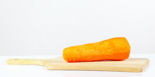 Fresh raw carrot on a cutting board. Closeup Stock Photo