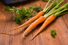 Fresh raw carrot. Ripe fresh raw carrot with leaf on wooden background Royalty Free Stock Photos
