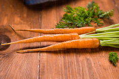 Fresh raw carrot. Ripe fresh raw carrot with leaf on wooden background Stock Photo