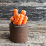 Fresh raw carrots in clay jar on old wooden background. Fresh raw carrots in clay jar on wooden background Royalty Free Stock Images
