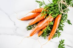 Fresh raw carrots. With green leaves, white marble background copy space top view Royalty Free Stock Photos