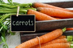 Fresh raw carrots with leaves in a box. With a small chalkboard on a wooden table Royalty Free Stock Photo