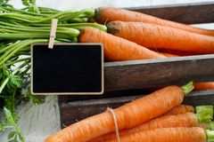 Fresh raw carrots with leaves in a box. With a small chalkboard on a wooden table Stock Images