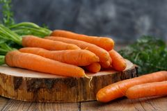 Fresh raw carrots with leaves. On a wooden table Stock Photo