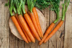 Fresh raw carrots with leaves. On a  wooden table Royalty Free Stock Image
