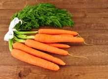 Fresh Raw Carrots With Tops. On a rustic wood background Stock Photos