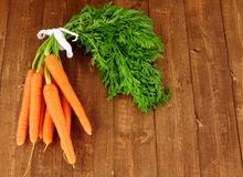 Fresh Raw Carrots With Tops. On a rustic wood background Stock Photography