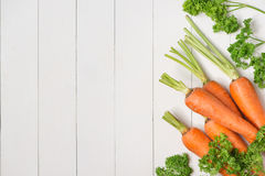 Fresh raw carrots with vegetables on wooden table. Fresh raw carrots with vegetables on wooden table Royalty Free Stock Photo