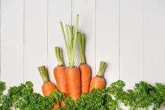 Fresh raw carrots with vegetables on wooden table. Fresh raw carrots with vegetables on wooden table Stock Photos