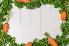 Fresh raw carrots with vegetables on wooden table. Stock Photography