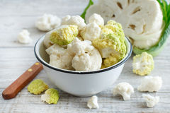 Fresh raw cauliflower. In a bowl on an old wooden table Stock Photos