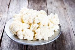 Fresh raw cauliflower in bowl. On a wooden table Stock Photos