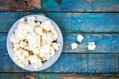 Fresh raw cauliflower in bowl. On a wooden table Stock Photo