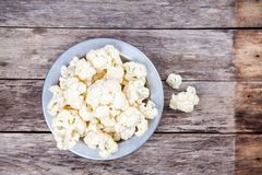 Fresh raw cauliflower in bowl. On a wooden table Royalty Free Stock Images