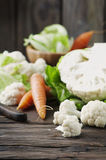 Fresh raw cauliflower and carrot on the wooden table. Selective focus Royalty Free Stock Photo