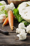 Fresh raw cauliflower and carrot on the wooden table. Selective focus Stock Photography