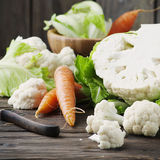 Fresh raw cauliflower and carrot on the wooden table. Selective focus and square image Royalty Free Stock Photography